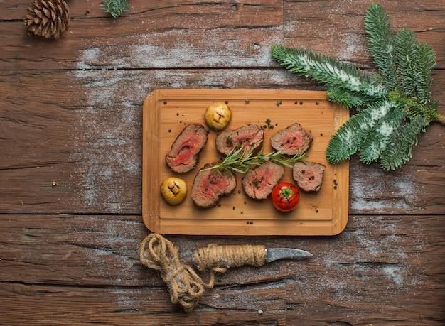 Gebratenes fleisch mit gemüse auf hölzernem brett