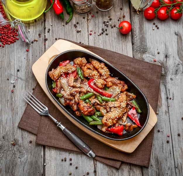 Gebratenes fleisch mit gemüse in einer pfanne