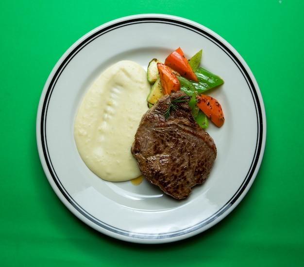 Gebratenes fleisch mit gemüse und sahnesauce