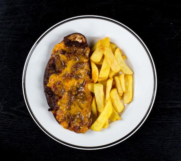 Gebratenes fleisch mit geriebenem käse und pommes frites