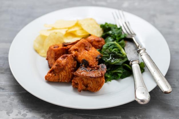 Gebratenes fleisch mit kartoffelchips und gemüse auf weißem teller