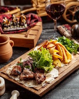 Gebratenes fleisch mit kartoffeln und glas rotwein