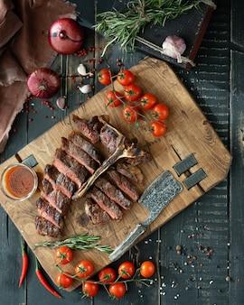 Gebratenes fleisch mit knochen und frischgemüse auf einem hölzernen schneidebrett in der rustikalen art