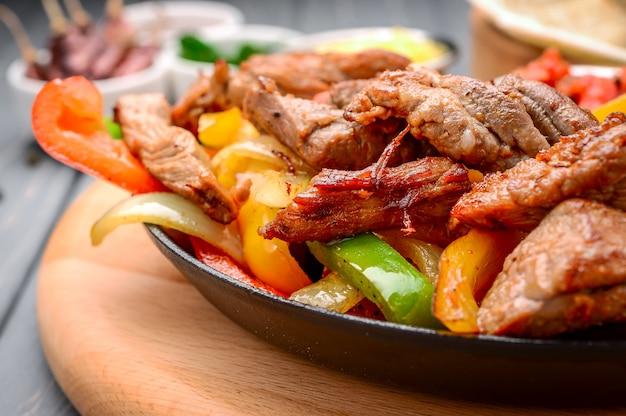 Gebratenes fleisch mit verschiedenem gemüse mit soße