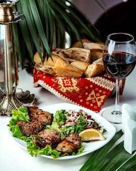 Gebratenes fleisch mit zwiebeln und zitrone und glas rotwein