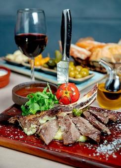Gebratenes fleisch serviert mit rucola gegrillten tomaten und einem glas wein
