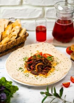 Gebratenes fleisch und gemüse mit kräutern auf einer weißen platte mit brotgemüse und glas wein
