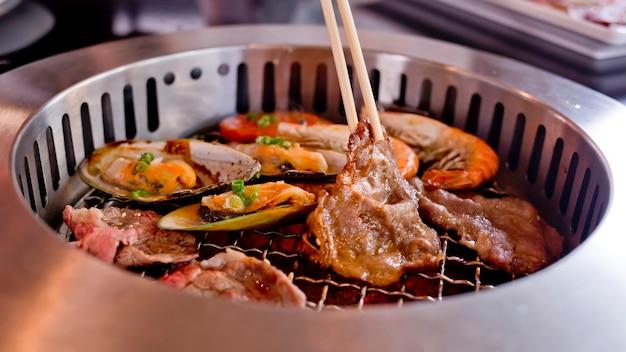Gebratenes fleisch und meeresfrüchte und essstäbchen auf dem bbq grill beim braten.