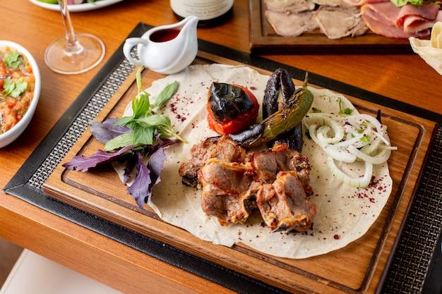 Gebratenes fleisch von oben mit gebratenen gemüseblättern und soße auf dem tischessenmahlzeit-abendessen-restaurant
