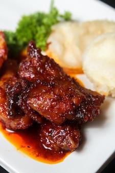 Gebratenes fleischgericht mit sauce, etwas gemüse und weißer sauce auf einem teller