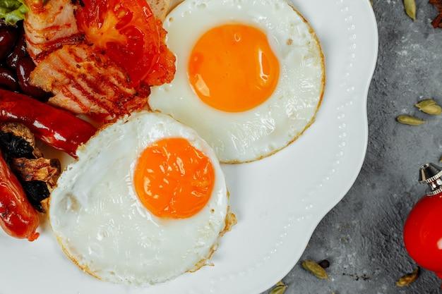 Gebratenes frühstück mit speck, würstchen und gebackenen bohnen.