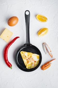 Gebratenes frühstücksomelett mit krabbenfleisch und käse, auf bratpfanne, auf weißem hintergrund, draufsicht flach legen