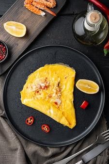 Gebratenes frühstücksomelett mit krabbenfleisch und käse, auf teller, auf schwarzem holztisch, draufsicht flach gelegt