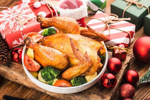 Gebratenes ganzes huhn mit weihnachtsdekoration.
