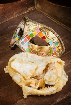 Gebratenes gebäck des italienischen karnevals mit venetianischer maske.