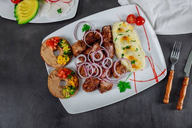 Gebratenes gegrilltes aufsteckspindelnschweinefleisch mit kartoffelpürees in der platte auf tabelle