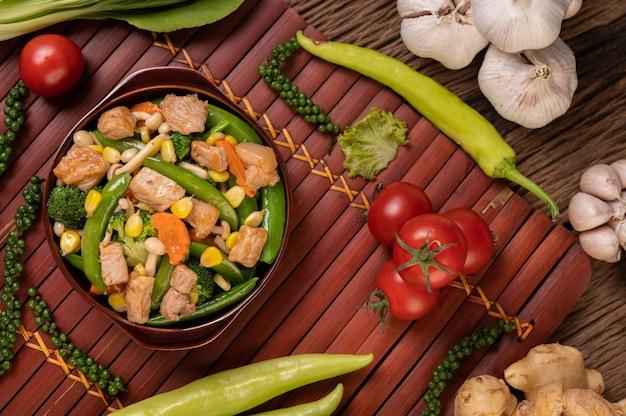 Gebratenes gemischtes gemüse mit grünen erbsen, karotten, pilzen, mais, brokkoli und schweinefleisch