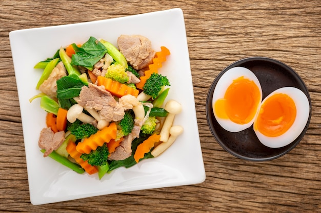 Gebratenes gemischtes gemüse mit schweinefleisch und shimeji-pilz neben gekochtem ei in keramikplatte auf rustikalem naturholzstrukturhintergrund, draufsicht