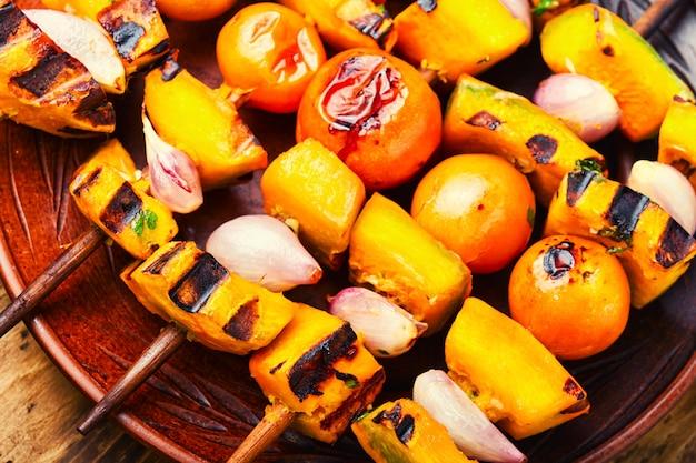 Gebratenes gemüse am spieß, gemüsespieß. kürbis, tomate, zucchini und paprika schaschlik