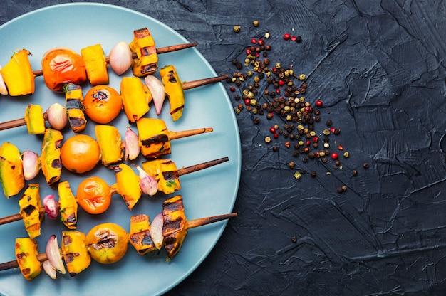 Gebratenes gemüse am spieß, vegetarischer spieß kebab. kürbis, tomate, zucchini und paprika schaschlik.platz für text