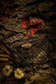 Gebratenes gemüse und äpfel auf einem grill auf einem hintergrund von baumrinde