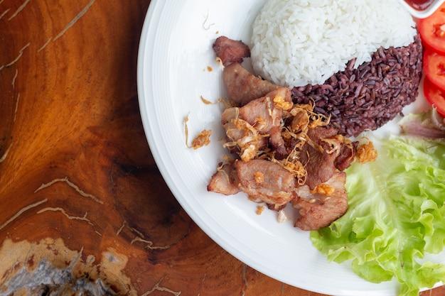 Gebratenes geschnittenes schweinefleisch mit knoblauch und pfeffer mit purpurrotem reis thailändische rezepte