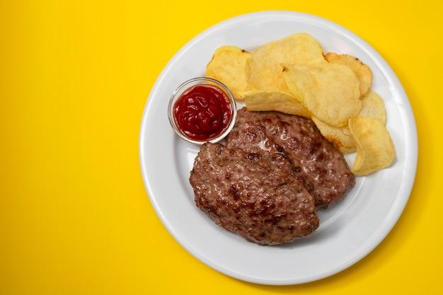 Gebratenes hackfleisch mit tomatensauce und kartoffelchips auf teller