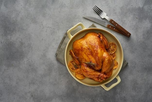 Gebratenes hausgemachtes hühnchen mit zitronen und rosmarin in einer auflaufform draufsicht mit kopierraum