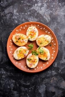 Gebratenes heißes gekochtes ei-masala ist ein beliebtes gesundes frühstück oder startermenü aus indien. mit zwiebeln, koriander, schwarzem pfeffer, tomate und salz über die hälfte der eier gestreut