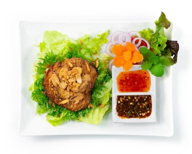 Gebratenes hühnchen auf knusprigem knoblauch thaifood style serviert chilisauce dekorieren geschnitzte karotten und gemüse draufsicht