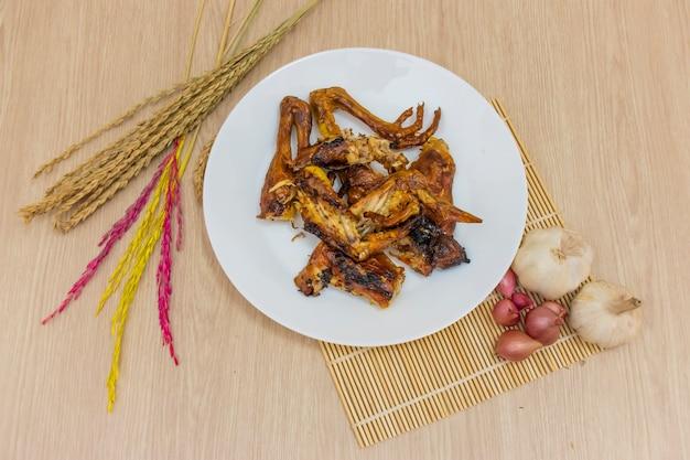 Gebratenes hühnchen in einem weißen teller wird auf den tisch gestellt und es liegen knoblauch, zwiebeln und reisähren herum.
