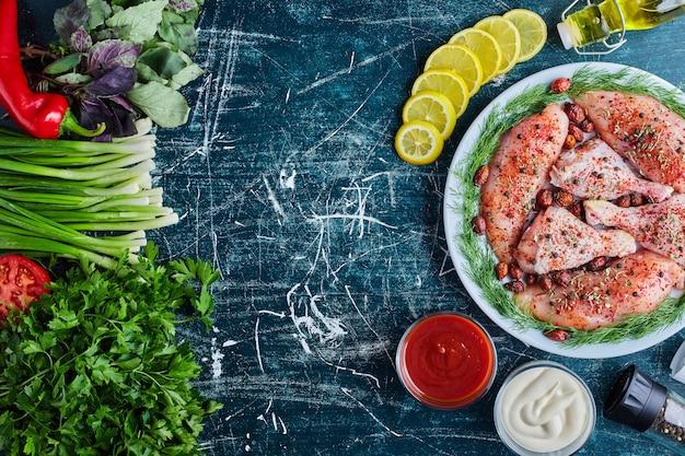 Gebratenes hühnerfleisch auf einem holzbrett mit saucen und gemüse.