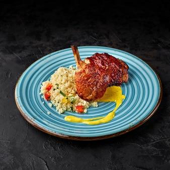 Gebratenes hühnerfleisch mit couscous, gewürzen und zitronengrassauce auf dunklem hintergrund