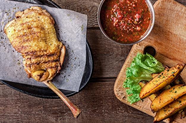 Gebratenes hühnerfleisch mit knochen, kartoffelschnitze, salat