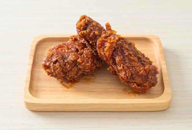 Gebratenes hühnerfleisch mit scharfer koreanischer sauce auf holzplatte