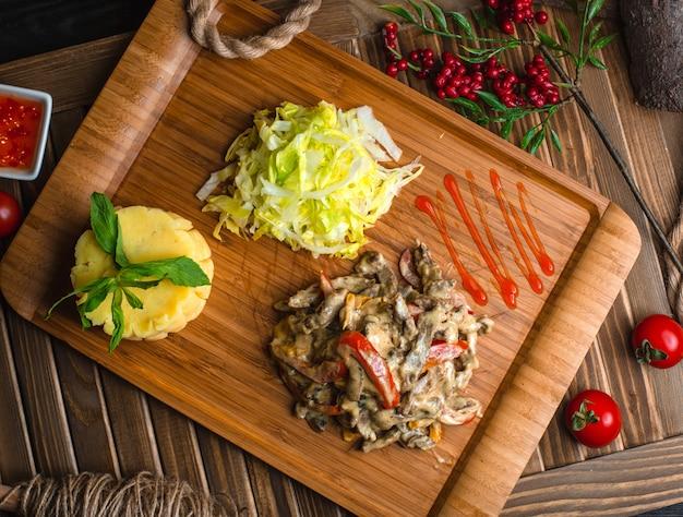 Gebratenes hühnerpilz mit gemüse auf hölzernem brett