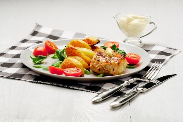 Gebratenes hühnerschnitzel mit kartoffelscheiben, serviert mit tomaten-kirsch-mais-salat. traditionelles belorussisches essen.