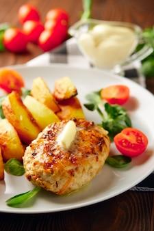 Gebratenes hühnerschnitzel mit kartoffelscheiben, serviert mit tomaten-kirsch-mais-salat.