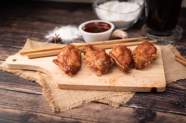Gebratenes huhn des heißen und würzigen koreanischen grills auf hölzernem schneidebrett