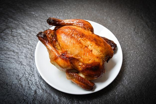 Gebratenes huhn - gebackenes ganzes huhn grillte auf weißer platte und dunklem hintergrund auf draufsicht