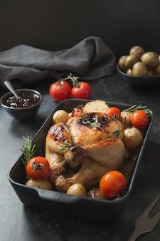 Gebratenes huhn mit kartoffel auf schwarzer tabelle.