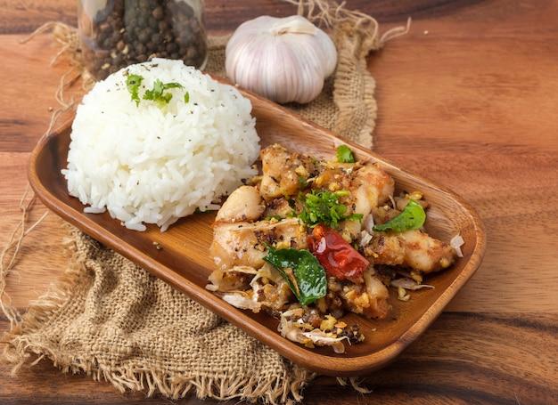Gebratenes huhn mit knoblauch und pfeffer mit reis. thailändisches gericht.