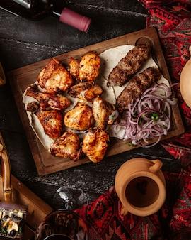 Gebratenes huhn mit lule-kebab und geschnittener zwiebel