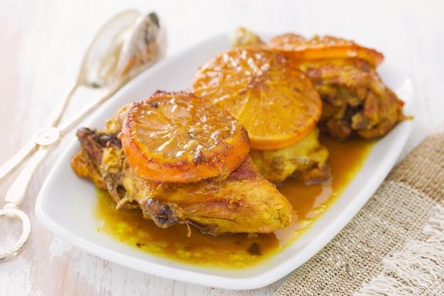 Gebratenes huhn mit orange auf weißem teller auf holz