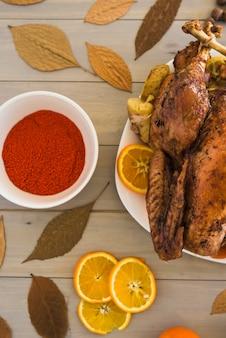 Gebratenes huhn mit orangen auf dem tisch