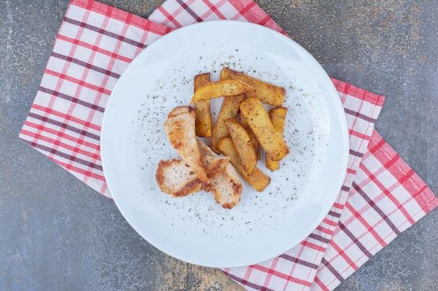 Gebratenes huhn und kartoffeln auf weißem teller. foto in hoher qualität