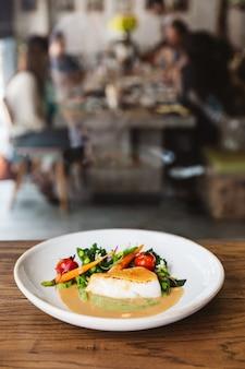 Gebratenes kabeljaufilet mit tomaten, bohnen und karotten in soßensauce. gedient in der weißen platte auf holztisch mit unschärfeleuten und speisetische