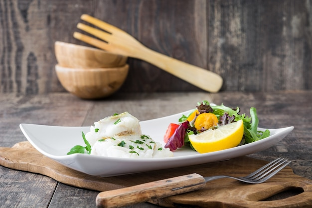 Gebratenes kabeljaufilet und -salat auf holztisch
