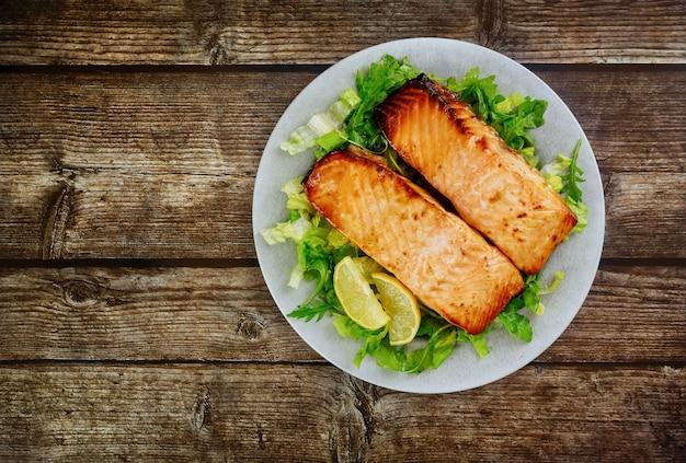Gebratenes lachsfilet mit grünem salat auf grauem teller. gesundes essen.