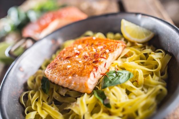 Gebratenes lachsfilet mit pasta tagliatelle zitrone und basilikum.